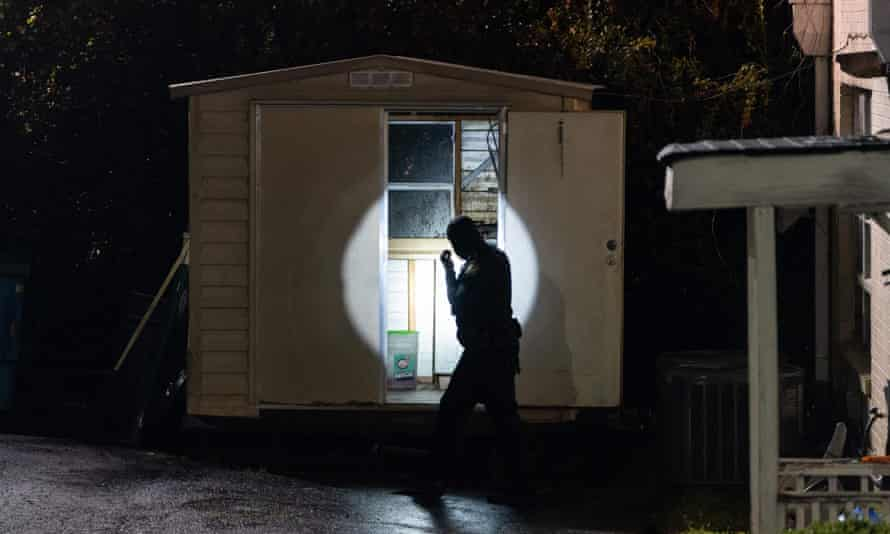 A police officer uses a flashlight to look in a shed outside a massage parlor where three people were shot and killed on Tuesday in Atlanta, Georgia.