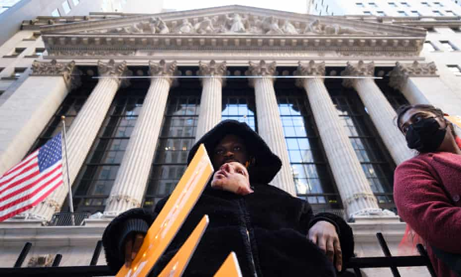 An activist holds a mask in his mouth during an 'eat the rich' protest outside the New York stock exchange in January