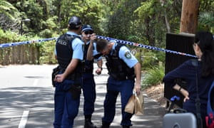 NSW police hold evidence bags at the scene of a double stabbing at the Church of Scientology headquarters at Chatswood in Sydney.