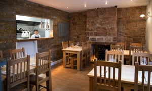 Burnt Truffle's dining room with bare brick walls and plain wooden tables and chairs