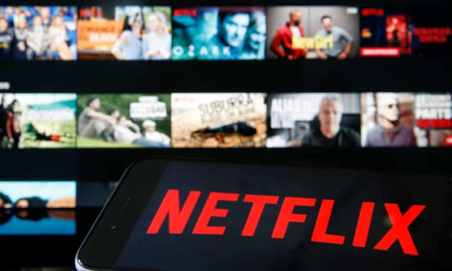 Netflix media service provider's logo is displayed on the screen of an iPhone in front of a television screen