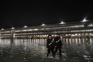 Police patrol across the flooded St. Mark's square