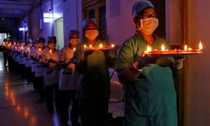 Healthcare workers at a Kolkata hospital carry candles and oil lamps to show solidarity with people affected by coronavirus.