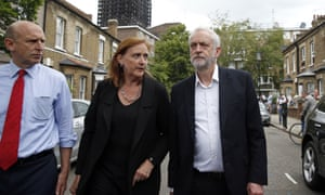 Britain's Labour Party leader Jeremy Corbyn, right, walks down a street during a visit to the scene of Grenfell Tower fire