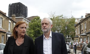 Jeremy Corbyn walks down a street in north Kensington with Grenfell Tower in the background