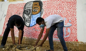Sudanese volunteers, wearing protective face masks, clear debris from a street in the capital Khartoum on April 8, 2020, during a COVID-19 awareness-raising campaign. Photo by ASHRAF SHAZLY/AFP via Getty Images.
