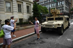 Independence Day revellers pose in front of a military Humvee parked on a street in the capital