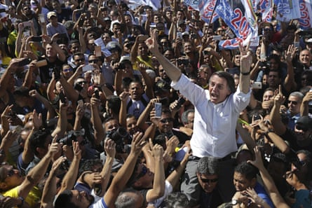 Jair Bolsonaro greets supporters as he gets a shoulder ride in Brasilia's Ceilandia neighbourhood the day before the attack
