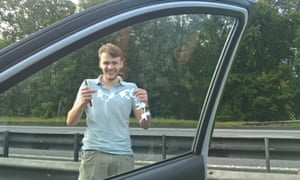 Man makes paper chain dolls on motorway.