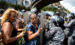 People confront riot police during a protest in Caracas against the shortage of food.