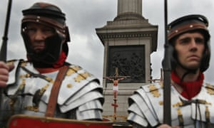 Actor James Burke-Dunsmore hangs on the cross in front of Nelson's Column in Trafalgar Square.
