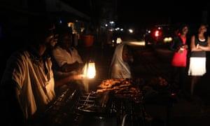Ugandan people prepare food by candlelight