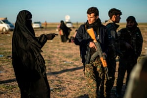 A member of the Kurdish-led Syrian Democratic Forces speaks with a woman leaving the Islamic Stategroup's last holdout of Baghouz, 1 March 2019.