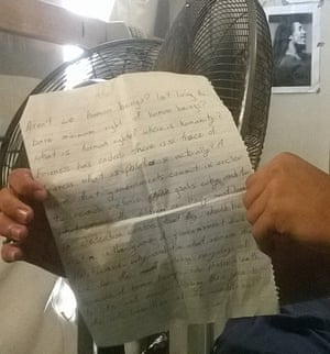 An asylum seeker holds a letter asking for the school to remain open