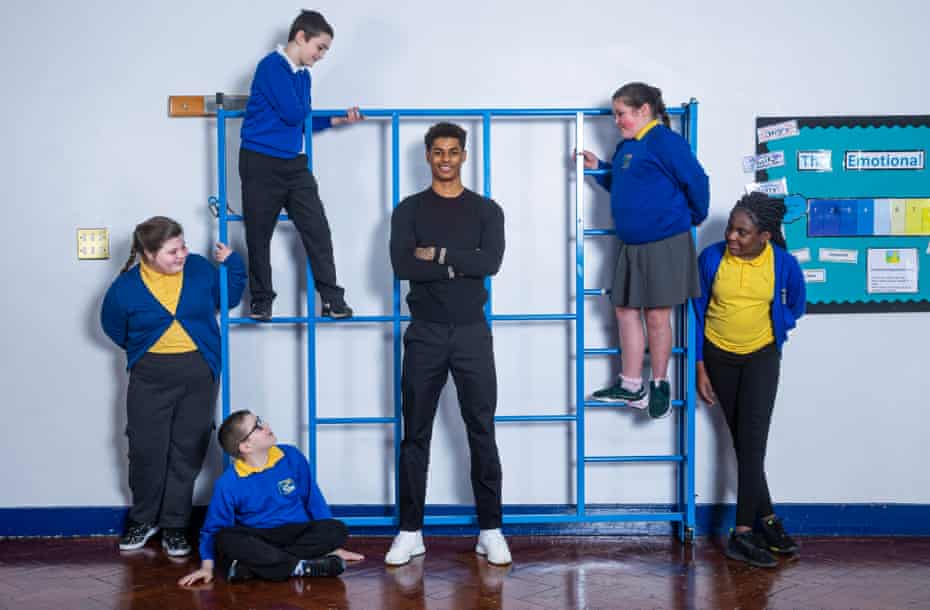 Marcus Rashford standing in front of a climbing frame with pupils at his former primary school