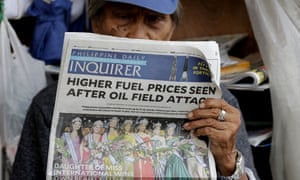 A sidewalk vendor reads a newspaper that headlines the recent attacks of Saudi oil refinery and raises global concern for a possible spike of oil prices Tuesday, Sept. 17, 2019, in Manila, Philippines.