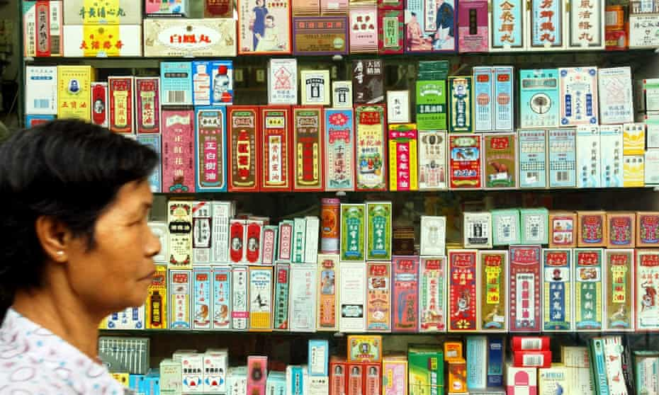 A pedestrian walks past a display stacked with Chinese medicine packages in Hong Kong
