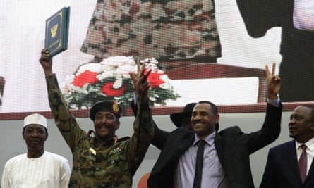 Ahmed L- Rabie (second right), gives the victory gesture alongside Gen Abdel Fattah al-Burhan (C), the chief of Sudan's ruling Transitional Military Council after the deal was signed.