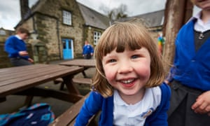 child in playground smiling at camera