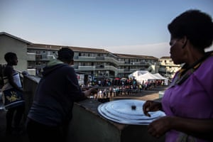 Residents at a former hostel complex watch voters queuing at a polling station in the Kwamashu township, on the outskirts of Durban