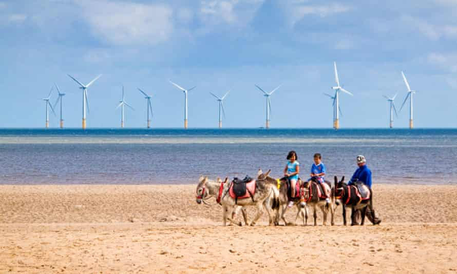 Children ride donkeys on Skegness beach with offshore wind turbines pictured in the background