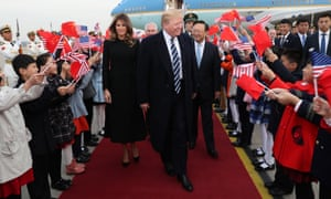 Donald Trump and Melania Trump are greeted by flag-waving children after touching down in Air Force One.
