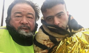 ai weiwei with a young man wrapped in blankets in human flow