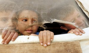 Syrian children look out from their tent in Lebanon