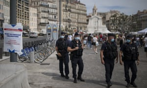 French riot police officers helping to enforce the wearing face masks in Marseille.