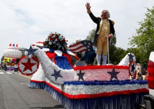 A man dressed as George Washington waves from a float
