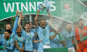 Manchester City players celebrate with the trophy after winning the Carabao Cup final against Chelsea.