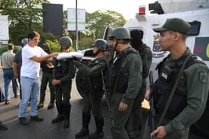 A man distributes food to soldiers in Caracas