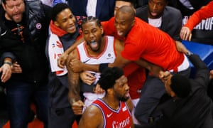 Kawhi Leonard is swamped by teammates after his shot beat the 76ers in Game 7 of the Eastern Conference semi-finals