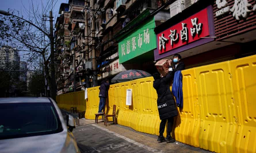 Residents pay for groceries over barriers set up to ring fence a wet market on a street in Wuhan, Hubei province, the centre of China's coronavirus disease outbreak
