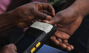 An electoral officer scans the thumb of a voter using a biometric system at a polling station in Lagos.