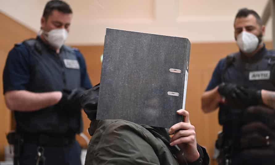 A defendant hides his face as he sits in the courtroom at Stammheim prison in Stuttgart.
