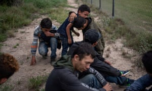 A four-year-old boy weeps in the arms of his uncle as he and others were apprehended by border control agents near the US border.