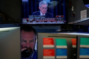 A trader on the floor of the New York stock exchange, with a screen showing Federal Reserve Chairman Jerome Powell's news conference.