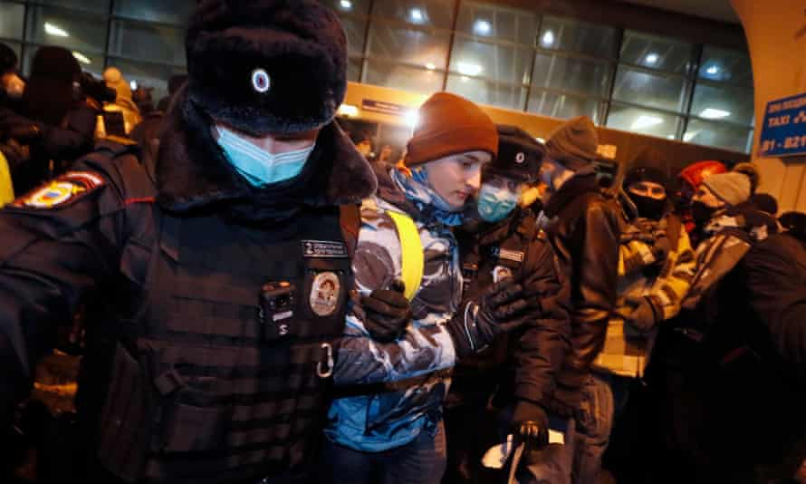 Police officers detain a Navalny supporter
