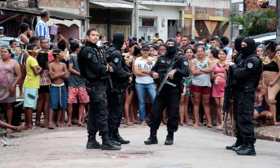 Policemen guard a site where, according to local media, an armed group entered and opened fire at a bar, killing 11, in Belem, Para state, Brazil.