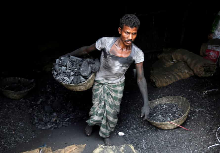 A worker carries coal in a basket in a industrial area in Mumbai.