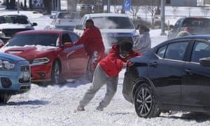 People push a car free after spinning out in the snow in Waco, Texas.