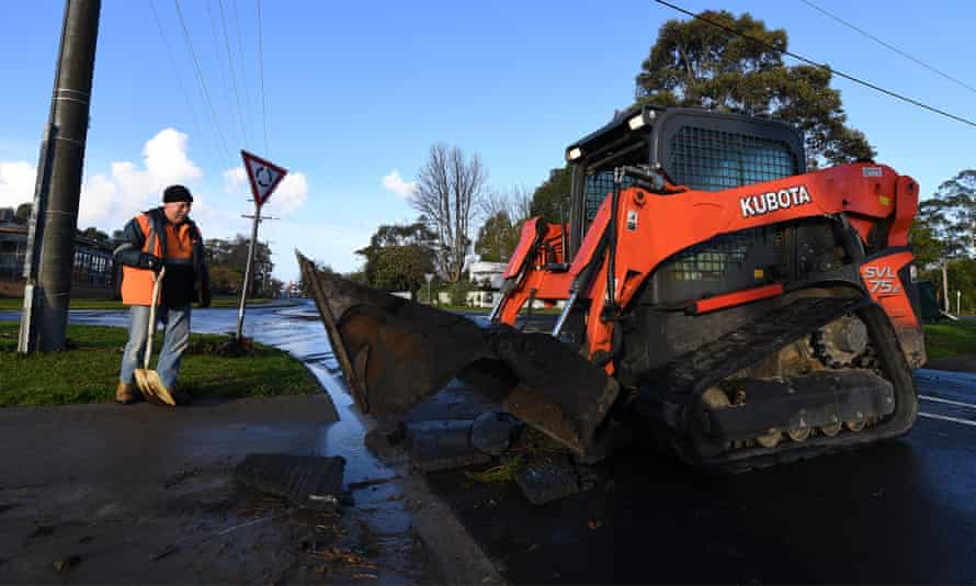 A construction worker and machinery clear mud off a street.