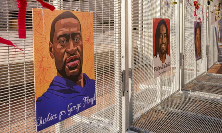 Portraits of black people killed by police are seen on a fence around the Hennepin County Courthouse.