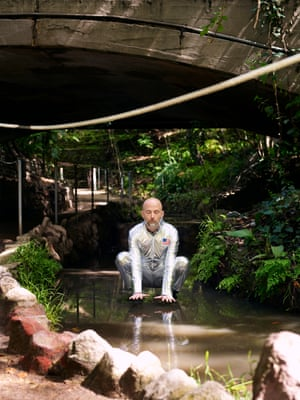 Moby appearing to hover above a stream, wearing a silver space suit