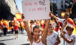 """A girl holds a placard saying """"Leave the children in peace"""" at a pro-unity rally in Barcelona on October 8."""