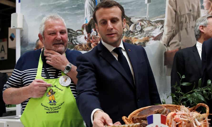 French president Emmanuel Macron speaks with fishermen at the 57th annual farmers' fair in Paris.
