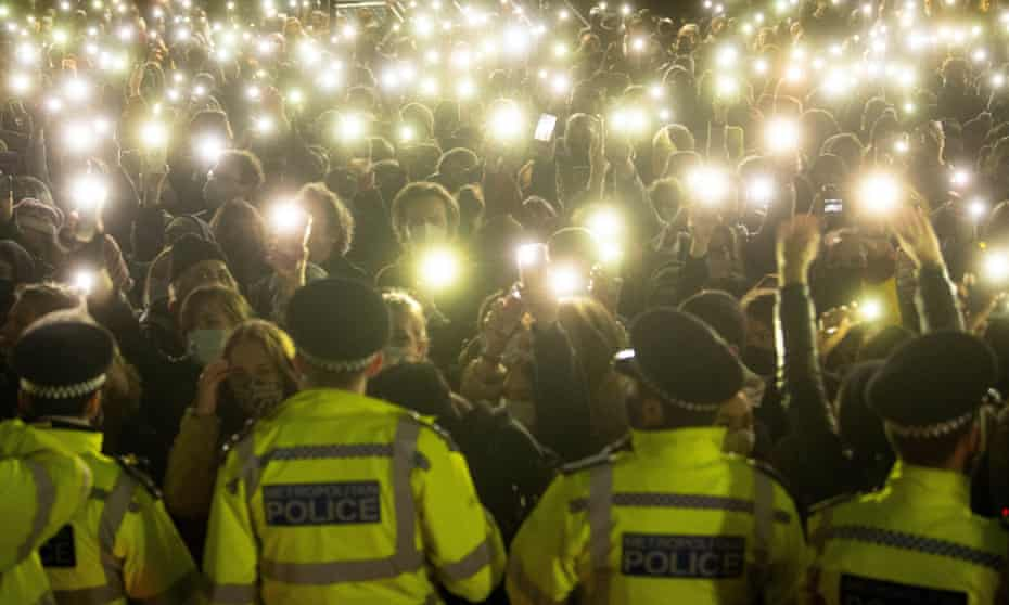 Women shining their phones at police officers on Clapham Common, London.