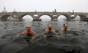 Participants take part in the traditional Three Kings swim alongside the medieval Charles bridge in Prague, Czech Republic
