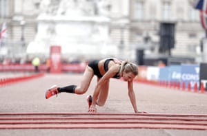British runner Hayley Carruthers crawls to the finish line at the end of the elite women's race during the 39th London marathon.